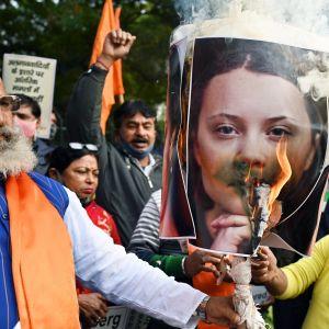 Mielenosoittajat sytyttävät tuleen Greta Thunbergin kuvaa.