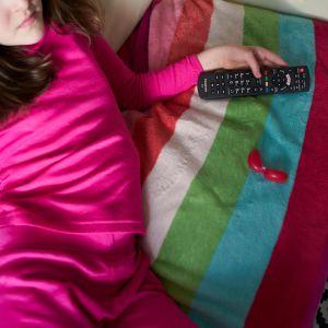 Nuori nainen katsoo telkkaria kaukosäädin kädessään