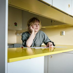 Arkkitehtiliitto SAFASn puheenjohtaja Henna Helander nojaa kyynerpäähänsäö keittiötason äärellä ja katsoo ulos ikkunasta.