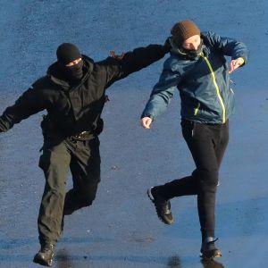 Poliisi ottaa mielenosoittajan niskasta kiinni.