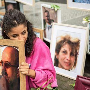 Syyrialainen Wafa Mustafa pitelee kadonneen isänsä kuvaa mielenosoituksessa Koblenzissa Saksassa.