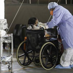 Hoitaja suojautuneena hoitamassa mahdollista koronapotilasta tammikuussa ulos pystytetyllä osastolla Steve Biko -sairaalassa Pretoriassa, Etelä-Afrikassa.