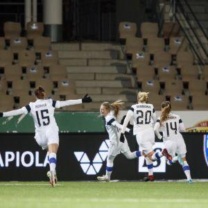 Suomen naisten jalkapallomaajoukkueen pelaajat iloitsevat kentällä.