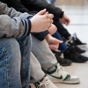 Yläkoululaisia istumassa penkillä