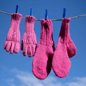 Pinkit villasormikkaat ja -sukat on ripustettu narulle kuivumaan. Takana sinistä taivasta.