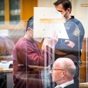 Eyad al-Gharib peittää kasvonsa oikeussalissa Saksassa.