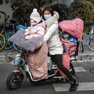 Nainen kuljettaa kahta lasta skootterin kyydissä Pekingissä.