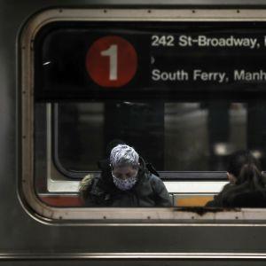 Kasvomaskiin pukeutunut matkustaja New Yorkin metrossa.
