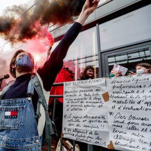 Opiskelijat osoittavat mieltään koronarajoituksia vastaan.