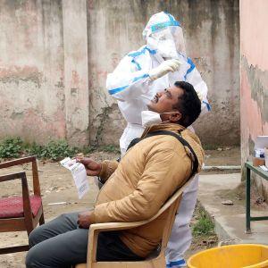 Suojavarusteisiin pukeutunut terveystyöntekijä tekee koronavirustestiä.