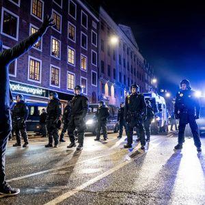 Protestoija seisoo poliisien edessä.