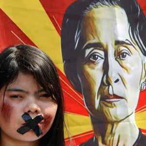 Suu Kyin kannattaja on teipannut suunsa kiinni, taustalla Suu Kyin kuva bannerissa.