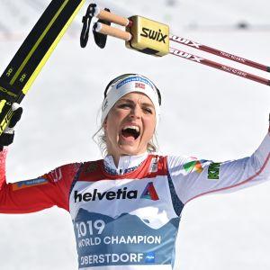 Therese Johaug tuulettaa MM-kultaa sukset ja sauvat käsissään.