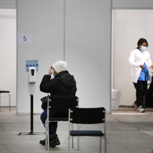 Asiakas odottaa rokotusvuoroaan Helsingin kaupungin keskiviikkona avautuneessa koronarokotuspisteessä Helsingin Messukeskuksessa 17. helmikuuta.