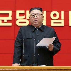 Kuvassa Kim Jong-un seisaallaan paperi kädessään. Taustalla seinässä on koreankielistä kirjoitusta.