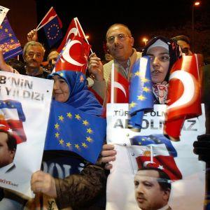 Ihmisiä heiluttelemassa pääministeri Erdoganin kuvia ja EU-lippuja.