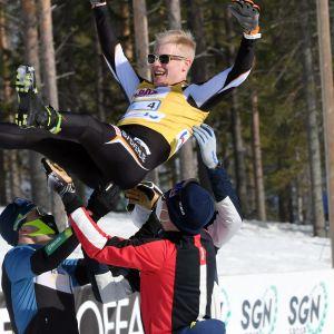 Puijon Hiihtoseuran Joonas Sarkkinen (vas.), Iivo Niskanen (oik.) ja Perttu Hyvärinen (takana) heittävät ankkuri Petteri Koiviston ilmaan