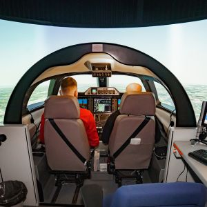 Kaksi lentäjäksi opiskelevaa lentosimulaattorissa.
