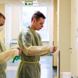 Varusmieslääkintämiehet pukevat suojavarusteitaan Länsi-Tallinnan keskussairaalan koronaosastolla.
