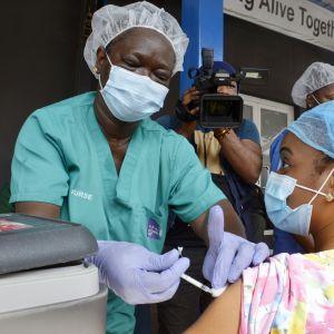 Sairaanhoitaja saa ensimmäisen rokoteannoksensa Nigerian lagosissa.
