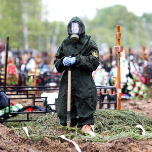 Suojavarusteisiin pukeutunut työntekijä  hautausmaalla Moskovassa.