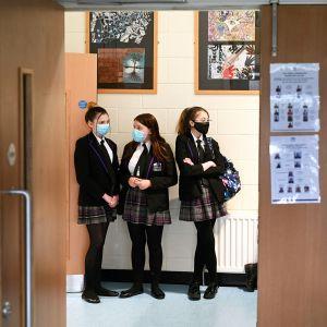 Kasvomaskeihin pukeutuneet opiskelijat jonottavat koulun käytävällä.