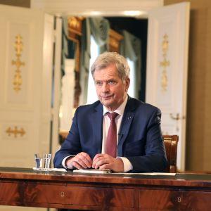 Sauli Niinistö istuu työpöytänsä ääressä.