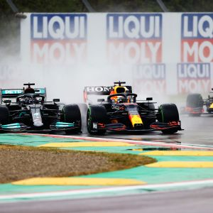 Lewis Hamilton ja Max Verstappen ajavat rinnakkain. Autoista nousee sadepatsas.