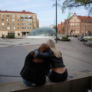 Kaksi malmölaistä nuorta tyttöä halaa toisiaan ulkona.
