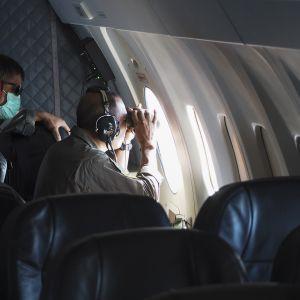 Indonesian laivaston lentokoneen miehistö kiikaroi koneen ikkunasta.