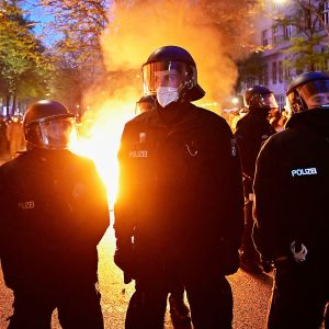 Mellakkapoliisit seisovat rivissä kadulle sytytetyn tulipalon vieressä.