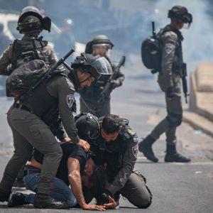 Kuvassa kaksi poliisia on painanut palestiinalaisen miehen katuun.