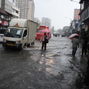 Ihmsiä ja autoja kadulla noin nilkan korkuisessa vedessä.