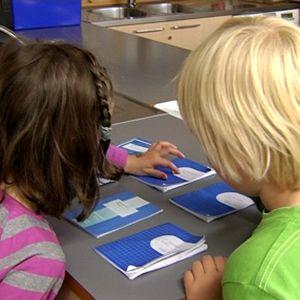 tyttö ja poika tutkivat kouluvihkoja