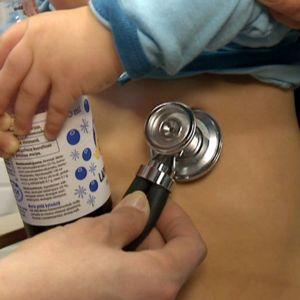 Lääkäri kuuntelee stetoskoopilla lapsen hengitysääniä neuvolassa.