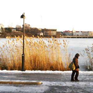 Nainen kävelee Töölönlahden rantatiellä.