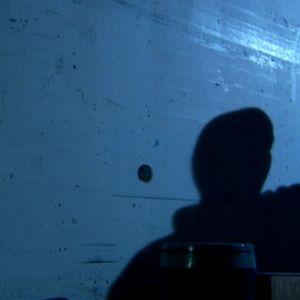Silhouettimainen hahmo pyyhkii seinää hämärässä valossa.