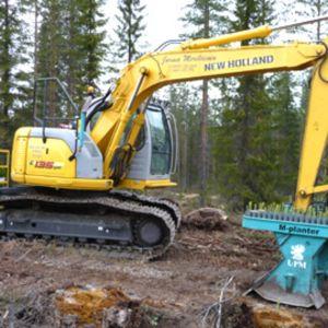 Kaivuriin rakennettu metsänistutuskone.