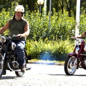 Kaksi miestä ajaa Jawa-moottoripyörillä.