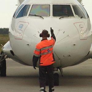 Kuvassa mekaanikko antamassa lentokoneelle peukku pystyyn - lähtölupaa