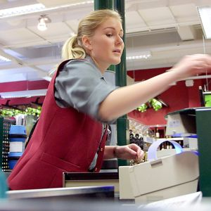 Nuori naismyyjä palvelee Alkossa.