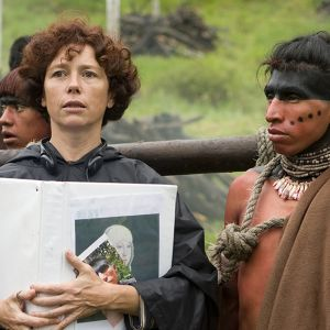 Nainen pitelee kansiota vierellään maskeerattu alkuperäisasukas elokuvan kuvauspaikalla elokuvassa.