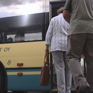 Ihmisiä nousemassa linja-autoon.
