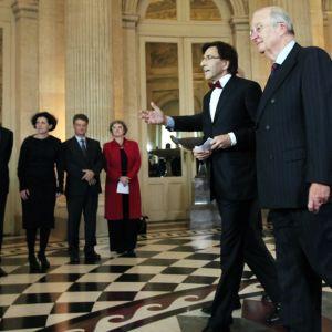 Ministerit seisovat rivissä, pääministeri ja kuningas kävelevät heidän edessään.