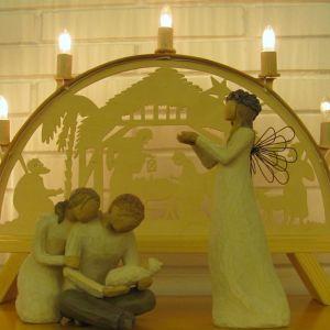 Puusta veistetyt Maria ja Joosef Jeesus-lapsen kanssa vierellään enkeli. Taustalla puinen kynttelikkö.