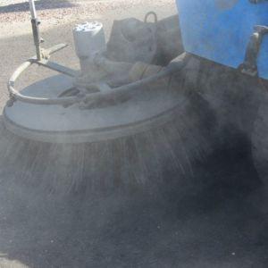 Lakaisukone poistaa hiekkaa kadulta.