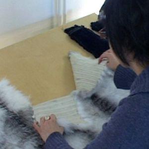 Kuvassa turkisalan opiskelija käsittelee kangasta ja turkiksia.