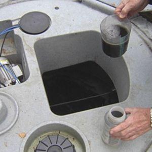 Mies ottaa vesinäytettä jäteveden puhdistamosta pihalla.