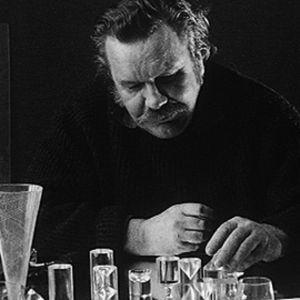 Arkistokuva Tapio Wirkkalasta, joka istuu työpöydän ääressä ja käsittelee lasiesineitä.