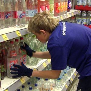 Nuori työharjoittelussa järjestää kaupan virvokejuomahyllyä.
